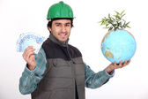 Tradesman holding a globe and a wad of money — Stock Photo