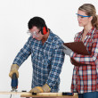 Man using band saw whilst woman supervises — Stock fotografie