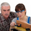 Experienced tradesman supervising his apprentice - Stock Photo