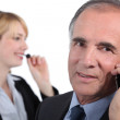 Senior executive with female assistant — Stock Photo #16487917