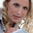 Eager young blond taking notes — Stock Photo