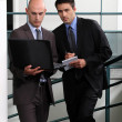 Businessmen comparing notes in stairwell — Stock Photo #16489395