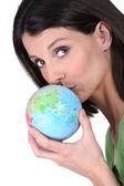 Woman kissing globe — Stock Photo