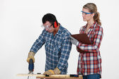 Man using band saw whilst woman supervises — Stock Photo
