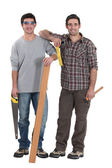 Two carpenters stood with plank of wood — Stock Photo