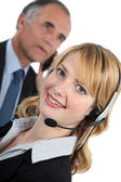 Young receptionist with headset and boss in background — Stock Photo