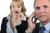 Boss and assistant making calls to customers — Stock Photo