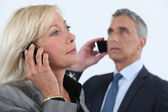 Businessman and businesswoman talking on their cells — Stock Photo
