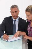 Secretary helping her boss fill in paperwork — Stock Photo
