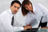 Two young business working all hours to finish project — Stock Photo
