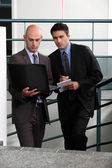 Businessmen comparing notes in stairwell — Stock Photo