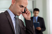 Businessmen negotiating over the phone — Stock Photo