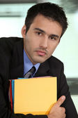 Eager young businessman falling behind with paper work — Stock Photo