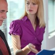 Businesswoman explaining document to colleague - Stock Photo