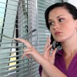 Woman peeking though window blinds — Stock Photo #16492093