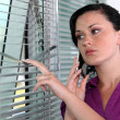 Stock Photo: Wompeeking though window blinds