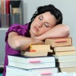 Overworked woman sleeping on a stack of books — Stok fotoğraf