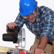 Carpenter using saw mounted to work surface — Stock Photo
