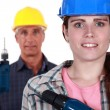 Man and woman holding power drills — Stockfoto