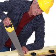 Construction worker sawing a plank of wood — Stock Photo #16494377