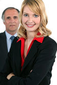 Young businesswoman in front of an older businessman — Stock Photo