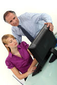 Businessman and secretary looking at the computer — Stock Photo