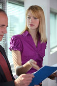 Businesswoman explaining document to colleague — Stock Photo