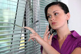 Woman peeking though window blinds — Stock Photo