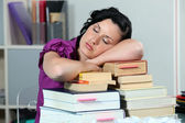 Overworked woman sleeping on a stack of books — Stock Photo