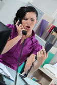 Stressed secretary answering two telephones — Stock Photo