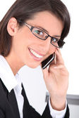 Smiling woman wearing trendy glasses and talking on a mobile phone — Stock Photo