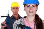 Man and woman holding power drills — Foto de Stock