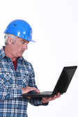 Mature craftsman working on his laptop — Stock Photo