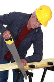 Construction worker sawing a plank of wood — Stock Photo