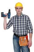 Carpenter drží vrtačku — Stock fotografie