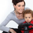 Woman and little boy on a toy car — Stock Photo
