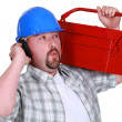 Craftsman wearing headphones and carrying a tool box - Photo