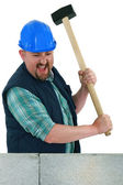 Man about to smash a wall using a mallet — Stock Photo