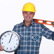 Carpenter all smiles holding ruler and clock — Stock Photo