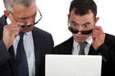 Two businessman taking their sunglasses to look at a laptop. — Stock Photo