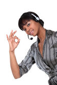 A businesswoman with a headset on making an ok sign. — Stock Photo
