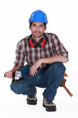 A kneeled handyman. — Stock Photo