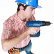 A construction worker holding a power tool — Stock Photo