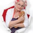 Elderly woman holding teddy — Stock Photo #16594387