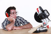 Bored man looking at circular saw — Stock Photo