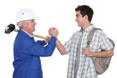 A handyman handshaking his trainee. — Stock Photo