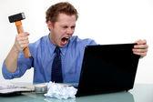 Ein geschäftsmann zu seinen laptop mit einem hammer zerschlagen. — Stockfoto