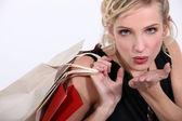 Vrouw met winkel zakken blaast een kus aan camera — Stockfoto