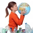 Little girl kissing planet earth next to her recycling — Stock Photo