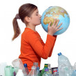 Little girl kissing planet earth next to her recycling — Stock Photo #16611911